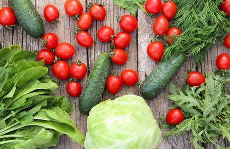 Fresh multi-colored vegetables rich in vitamins on  wooden background with place for text. Healthy fiber diet top view. Tomatoes, cucumbers, cabbage and greens