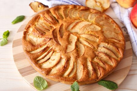 Traditional apple sliced fruit pie with honey and mint. Taten apples and pears on craft paper with a plate of honey Imagens