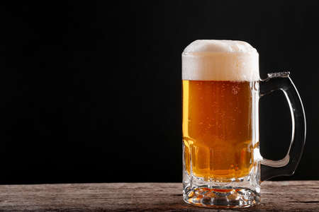 Unfiltered light beer in a glass on an old wooden table on a dark background with place for text Imagens