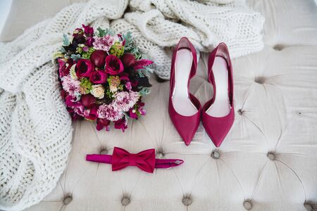 Bridal bouquet with red peonies, bow tie and red high-heeled shoes on a white pouffe, next to a knitted white blanket Banque d'images