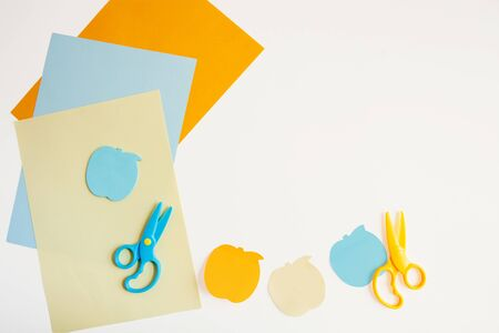 Several sheets of colored paper, two scissors, and Apple-shaped sticky notes on a white background. Flat layout with space for text