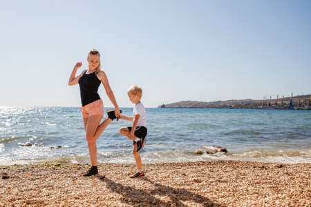 A young blonde mother and her blonde son play sports on the rocky beach in the summer