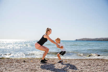 A young blonde mother and her blonde son play sports on the rocky beach in the summer Reklamní fotografie