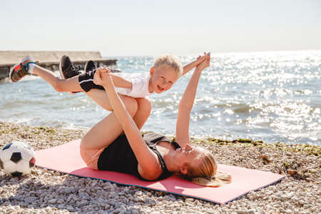 A young blonde mother plays sports with her blonde son on a Mat in the summer on the sea coast