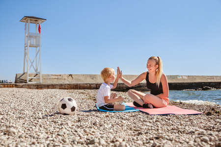A young blonde mother plays sports with her blonde son on a Mat in the summer on the sea coast Reklamní fotografie