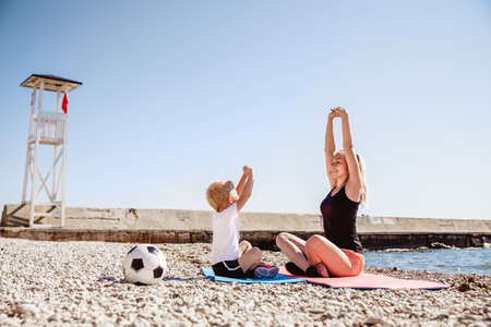 A young blonde mother and her blonde son play sports on a Mat on the rocky beach in the summer