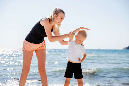 A young blonde mother teaches her young son sports exercises in the summer on the beach