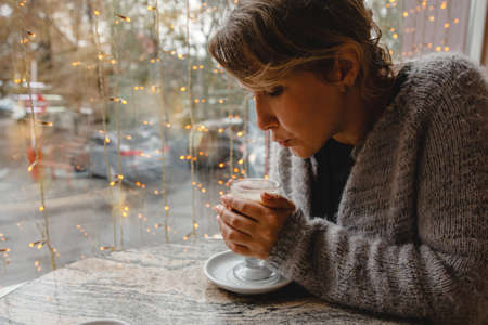 A young brown-haired woman in a warm jacket is sitting in cafe at a table by the window and blowing on a glass of coffee. High quality photo