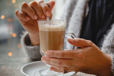 A woman in a warm jacket is sitting in a cafe at a table by the window and stirring coffee. Only hands are in the frame. High quality photo