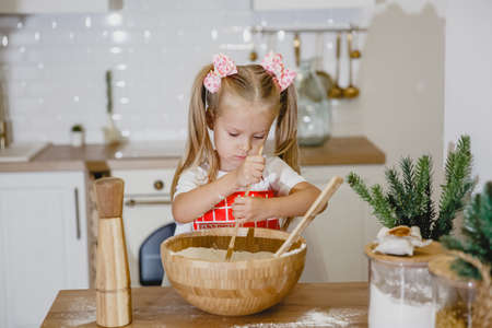 Four-year-old blonde girl in a white t-shirt and red apron kneads dough at home in the kitchen at a wooden table