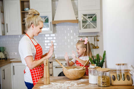 Blonde mom and daughter in red checkered aprons knead dough in the Christmas decorated kitchen at home