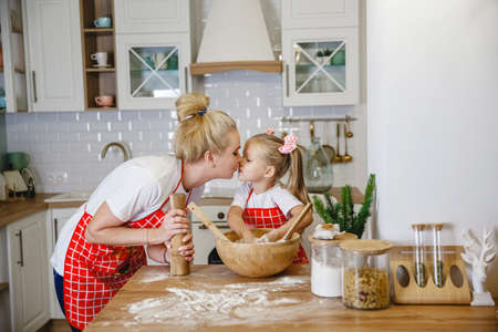 Blonde mom in a red apron kisses daughter during the preparation of the dough in the Christmas decorated kitchen at home Stok Fotoğraf
