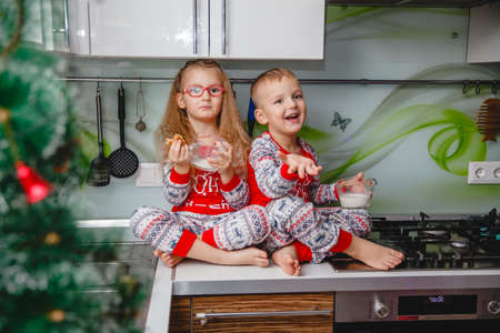 Little brother and sister sit on a Christmas-decorated kitchen table in pajamas and drink milk. Girl with glasses