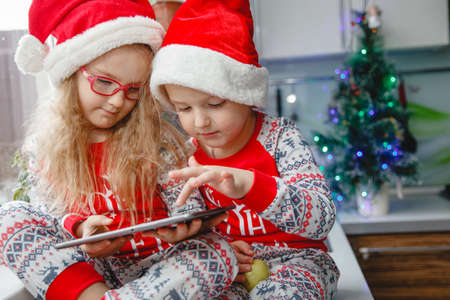 Brother and sister sit in the kitchen in Santa hats and look at the pad. Children write a letter to Santa Claus