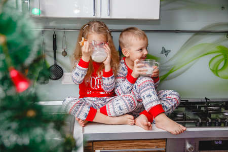 Little brother and sister sit on a Christmas-decorated kitchen table in pajamas and drink milk. Girl with glasses Stockfoto