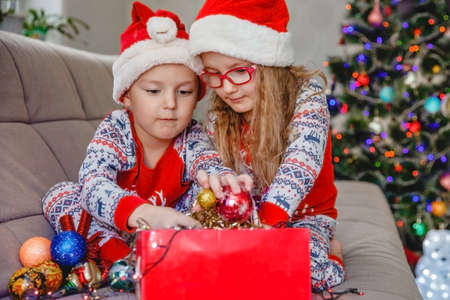 Little brother and sister in Santa hats on the sofa against the the Christmas tree take out decorations from the box