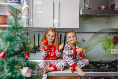 Little laughing twins sit on the table in pajamas in the Christmas decorated kitchen with an Apple. Girl with glasses