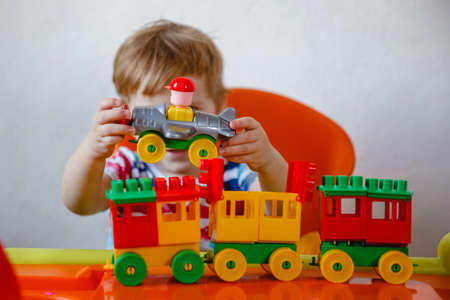 A small blond boy at home sitting at an orange childrens table playing a colorful plastic construction kit