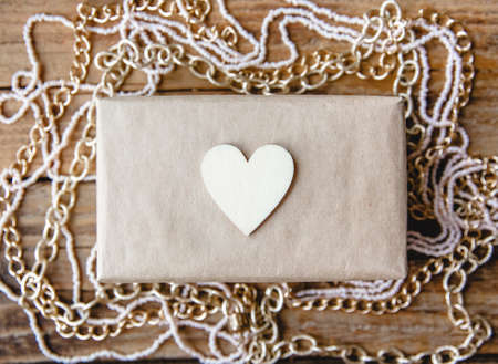 Gift box in craft paper decorated with a wooden heart on a wooden table among beads. Flat layout