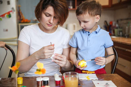 Mom and baby son decorate Easter eggs at home at the kitchen table
