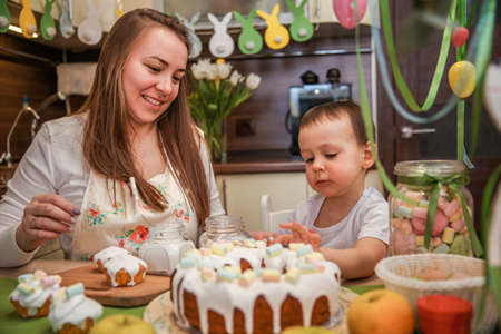 Mom and baby son decorate Easter cakes at home at the table in the decorated kitchen