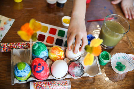The child takes one egg from the crafting stand on the table for Easter decorating. Only the hand is in the frame. High quality photo