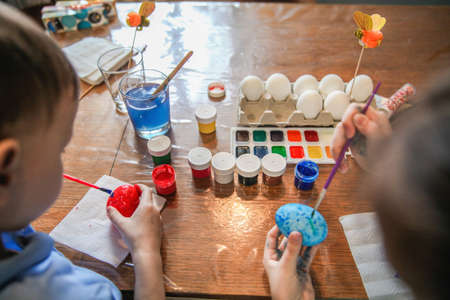 Children paint eggs for Easter sitting at the table. The view from the back. High quality photo