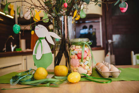Self-made white paper Easter bunny, marshmallow jar, ribbons, Easter eggs and apples on the table under the Easter tree. High quality photo