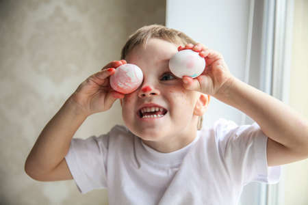 A four-year-old boy in a white T-shirt and a painted nose is fooling around trying on Easter eggs on his eyes. High quality photo