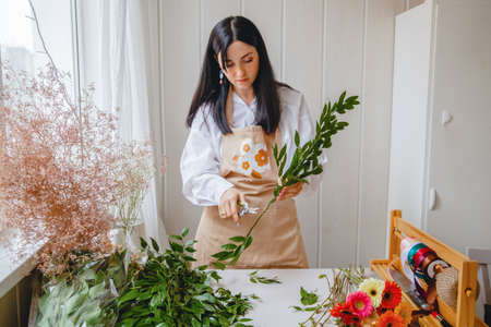 a young brunette woman florist in apron cuts leaves from the stems before starting to create a bouquet in her workshop Stockfoto