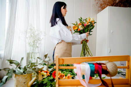 a young brunette woman in an apron in the process of creating a bouquet in the rustic style in her flower shop
