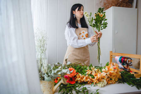 a young brunette woman in an apron in the process of creating a bouquet in the rustic style in her flower shop. High quality photo