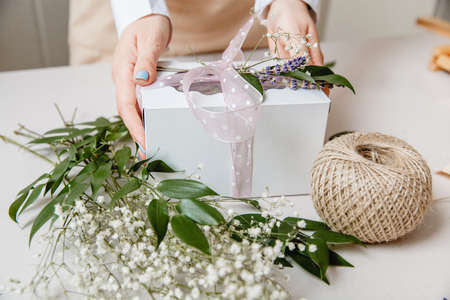A florist decorates a gift box with flowers and a ribbon on a white desktop. Only the hands are in the frame
