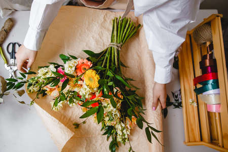 a female florist in a white shirt wraps a bouquet of fresh flowers in paper. Top view