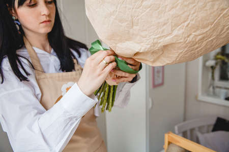 a brunette florist in an apron ties a bouquet of flowers wrapped in paper with a green ribbon