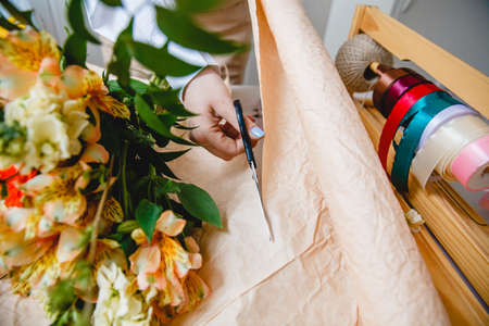 A florist cuts packaging paper with scissors on a desktop in a flower shop. On the paper is a bouquet of fresh flowers