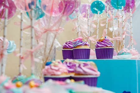 Lilac cupcakes and long lollipops with ribbons on a blue stand.