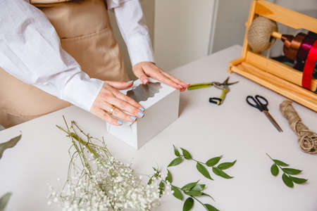 a female florist makes a white paper gift box on her desk in a flower shop Stockfoto
