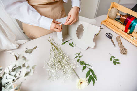 a female florist makes a white paper gift box on her desk in a flower shop. High quality photo