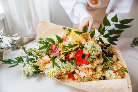 a female florist in a white shirt wraps a bouquet of fresh assorted colorful flowers in craft paper. Stockfoto