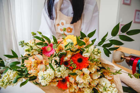A bouquet of colorful fresh flowers wrapped in paper on the florists desk. Florist in the background