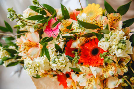 A bouquet of colorful fresh flowers wrapped in paper on the florists desk. Selective focus Stockfoto