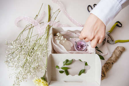 a female decorator puts a decorative pink candle in a white gift box. Nearby are flowers and florists tools. Top view Stockfoto