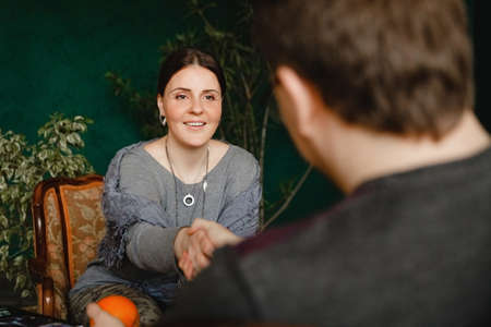 A young brunette european woman psychologist with a smile shakes hands with a patient sitting opposite her during an appointment in her office. High quality photo