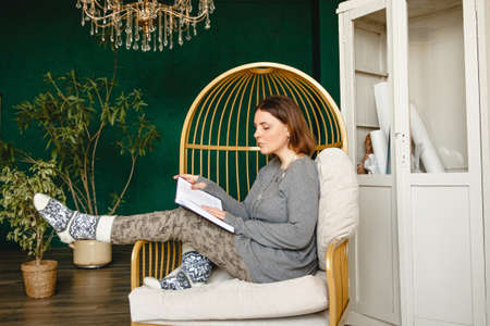 A young European brunette woman in home clothes and warm socks sits in a chair in a room with green walls and a large chandelier and reads a book. High quality photo Stock fotó