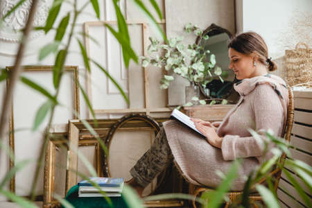 A young European brunette woman in a warm beige cardigan sits in a wicker chair by the window with her feet on a chair and reads a book. There are a lot of empty frames against the wall.