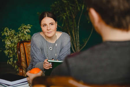 A brunette european woman psychologist conducts a patients appointment in office. She sits across and listens him Stockfoto