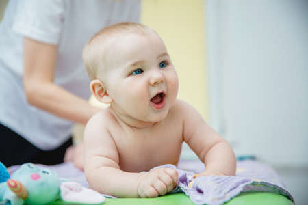 A small smiling child lying on his stomach gets a massage in a massage room. He has a toy in his mouth Stockfoto