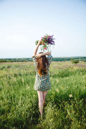 A young woman with long hair in a colorful short dress holds a bouquet in raised hands standing with her back Stockfoto