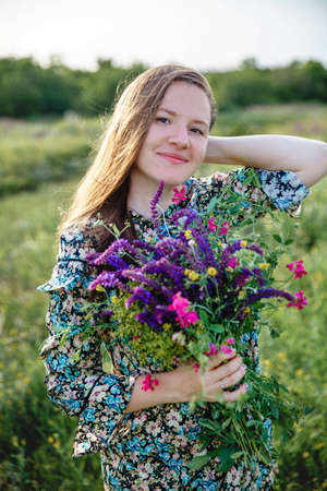 young beautiful long-haired blonde woman of European appearance with a blooming bouquet of wild flowers in her hands Stockfoto